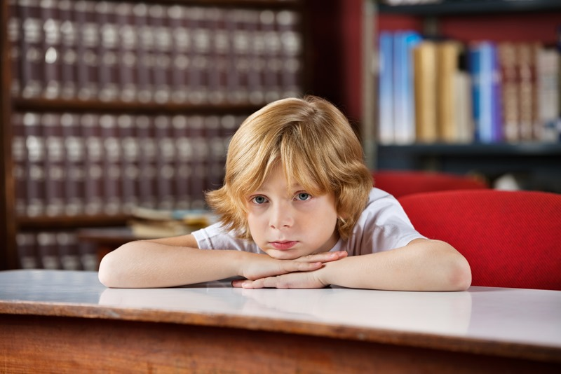 Bored Schoolboy Leaning On Table In Library
