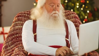 Santa claus typing on laptop at home in the living room